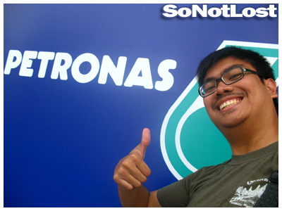 in front of the Petronas corporate logo